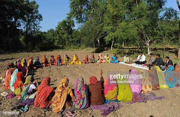 Officials from Indian organisation SKS Microfinance interact with borrowers at a gathering in the village of Vadod some 35kms from Ahmedabad on...