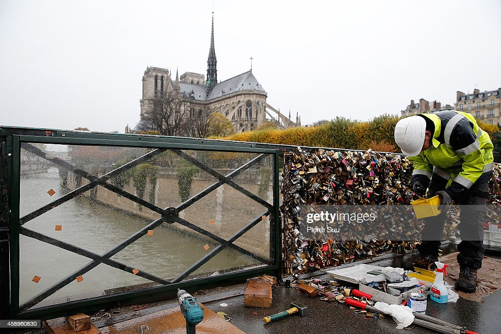 Officials from Paris City Hall place plastic panels on the Pont De L'Archeveche in order to prevent tourists from attaching love padlocks on November 14, 2014 in Paris, France.