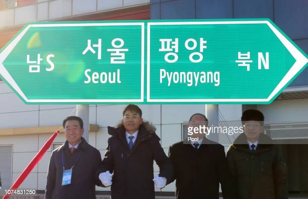 Officials from South and North Korea stand in front of a road sign during the ceremony for a project to modernize and connect roads and railways over...