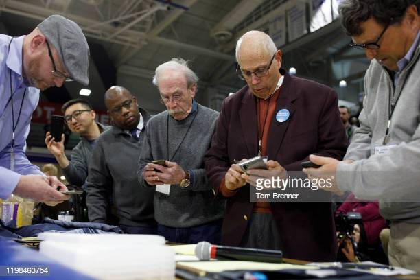 Officials from the 68th caucus precinct overlook the results of the first referendum count during a caucus event on February 3, 2020 at Drake...