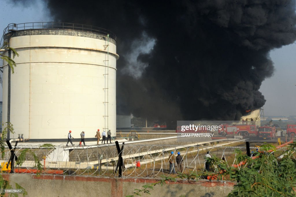 Officials from the Indian Oil Corporation (IOC) walk alongside a fuel tank as Indian fire fighters attempt to douse the flames of a burning fuel tank at the Indian Oil Corporation (IOC) plant at Hajira near Surat, some 275 kms from Ahmedabad on January 6, 2013. Three persons were killed in a major fire in a storage tank of IOC terminal, which was contained after a 21-hour operation by fire brigade team, officials said according to the Press Trust of India (PTI). AFP PHOTO / Sam PANTHAKY