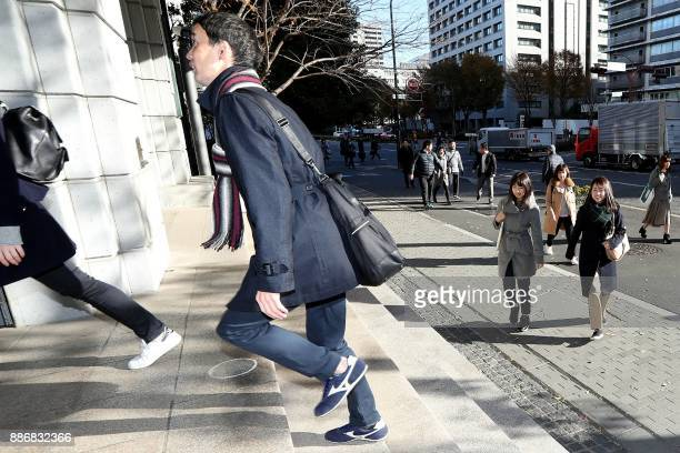 Officials from the Japan Sports Agency wear sneakers on their way to the office as part of a campaign to promote fitness in Tokyo on December 6 2017...