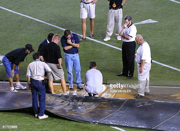 Officials from the National Football League and stadium personnel from Veterans Stadium in Philadelphia inspect the subsurface of the artificial turf...