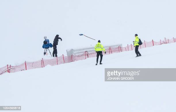 Officials gather beside a television camera at Solden on October 28 after the FIS Alpine Ski World Cup season opener on the Rettenbach glacier was...