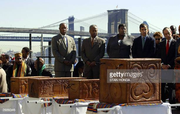 Officials including New York City Mayor Michael Bloomberg stand behind four coffins containing the remains of free and enslaved AfricanAmericans 03...