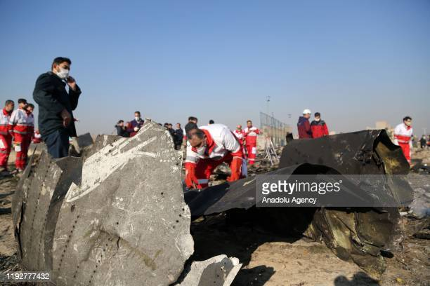 Officials inspect pieces of the plane at site after a Boeing 737 plane belonging to a Ukrainian International Airlines crashed near Imam Khomeini...
