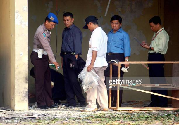 Officials inspect the bomb blast scene inside the police headquarters in Medan 05 April 2006 The strong accidental blast during a police bomb...