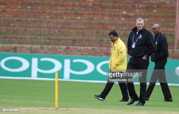 Officials inspect the pitch after rain delayed the ICC Cricket World Cup Qualifier Warm Up match between Zimbabwe and Ireland on February 27 2018 in...