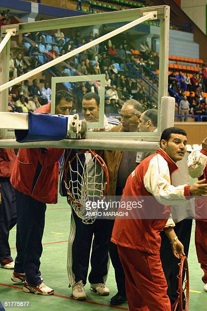Officials inspect the rim of the basket mount after it was broken by Egyptian player Sherif alDiyassi following a dunk during the 19th African clubs...