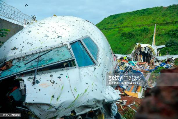 Officials inspect the wreckage of an Air India Express jet at Calicut International Airport in Karipur, Kerala, on August 8, 2020. - Fierce rain and...