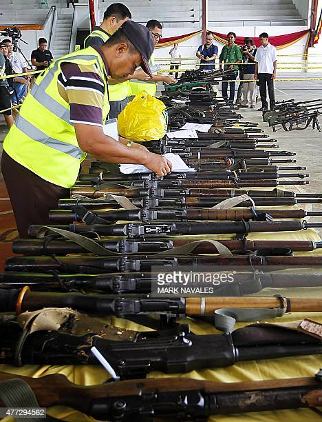 Officials inspect weapons handed over by the Moro Islamic Liberation Front rebel group for decommissioning in Sultan Kudarat on June 16 2015 The Moro...