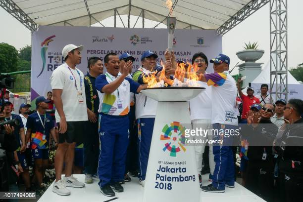 Officials light the 2018 Asian Games torch during the torch relay at National Monument in Jakarta Indonesia on August 16 2018 The 18th Asian Games is...