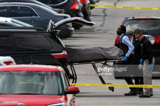 Officials load a body into a vehicle at the site of a mass shooting at a FedEx facility in Indianapolis, Indiana, on April 16, 2021. - A gunman has...