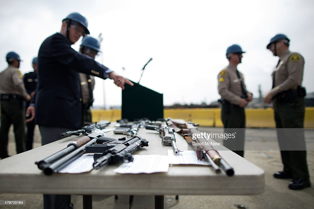 Officials look at confiscated guns prior to the destruction of approximately 3,400 guns and other weapons at the Los Angeles County Sheriffs' 22nd annual gun melt at Gerdau Steel Mill on July 6, 2015 in Rancho Cucamonga, California. The weapons, confiscated in various law enforcement operations, will be recycled in the form of steel rebar to be used in construction. California law requires the destruction of the confiscated weapons.