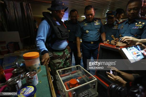 Officials look at the flight data recorder part of the illfated Lion Air flight JT 610's black box after it was recovered from the Java Sea during...