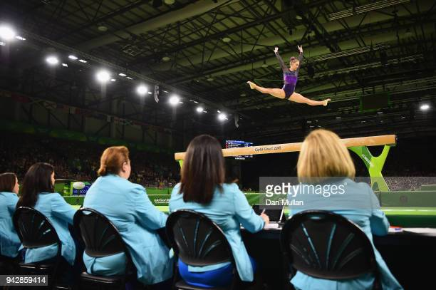 Officials look on as Cara Kennedy of Scotland competes on the beam in the Women's Individual AllAround Final during Gymnastics on day three of the...