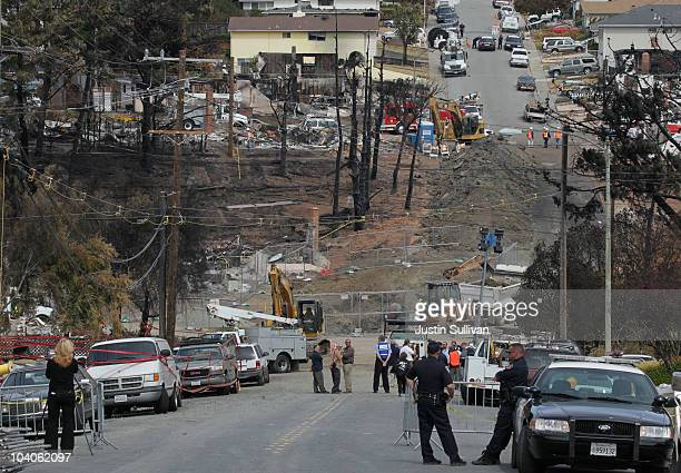 Officials look on as Pacific Gas Electric workers excavate the crater at the epicenter of a deadly gas main explosion September 13 2010 in San Bruno...