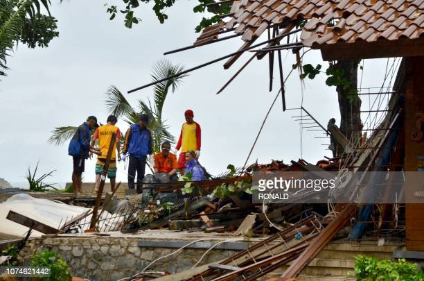 Officials look through the wreckage of damaged buildings in Carita on December 23 after the area was hit by a tsunami on December 22 following an...
