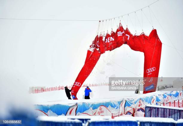 Officials manouver the finish line banner at Solden on October 28 after the FIS Alpine Ski World Cup season opener on the Rettenbach glacier was been...