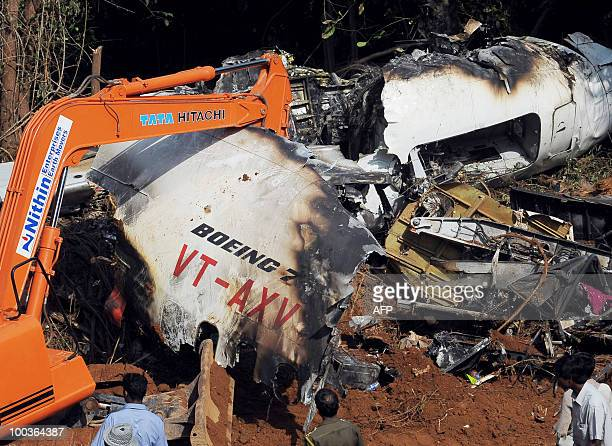 Officials of Air India and the Airports Authority of India work at the plane crash site of the Air India Express Boeing 737800 in Mangalore on May 24...