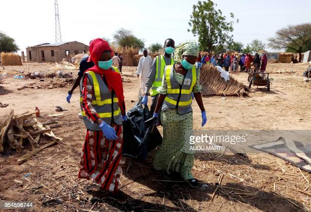 Officials of Borno State Emergency Management Agency carry the body of a victim of multiple suicide attacks to the ambulance in Maiduguri in...