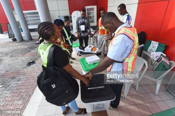 Officials of Independent National Electoral Commission hold hands to pray together against violence before voting began at a polling station in Port...