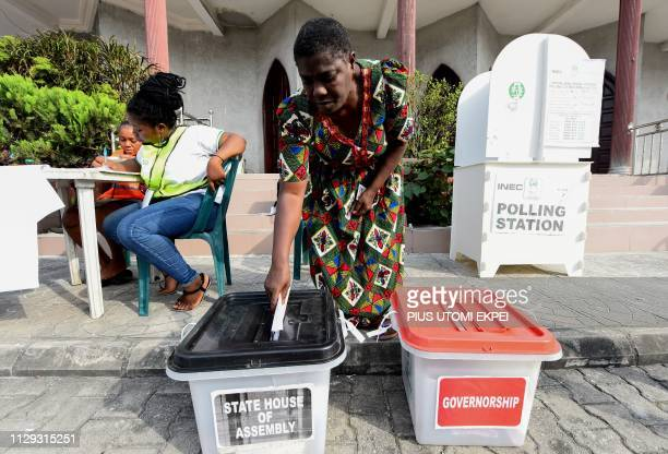 Officials of Nigeria's Independent National Electoral Commission look on as a woman casts her vote at a polling station in Port Harcourt Rivers State...