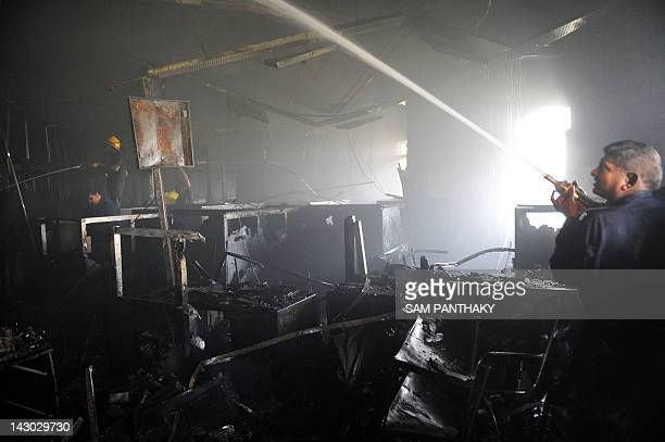 Officials of the Ahmedabad Fire and Emergency Services battle a fire in the building of Bharat Sanchar Nigam Ltd situated in Navrangpura area of...