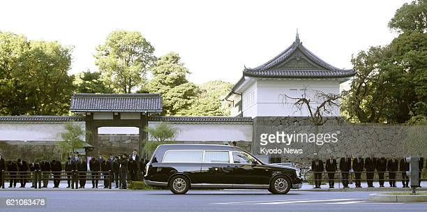 Officials of the Imperial Household Agency line up and bow as a hearse carrying Prince Mikasa an uncle of Emperor Akihito passes in front of the...
