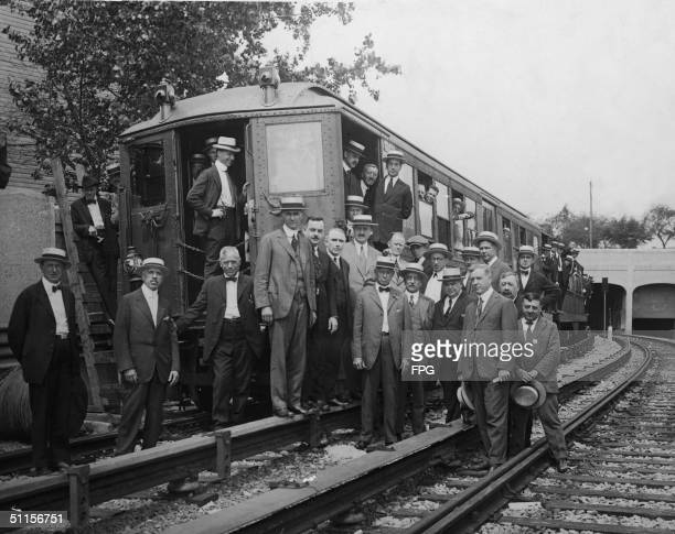 Officials of the Interborough and Public Service Commission stand in and a round a subway car on the IRT's Eastern Parkway Line around the time of...