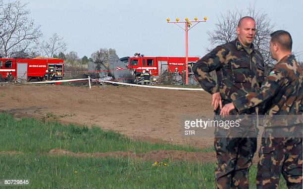 Officials of the local airbase reference on the field as rescue workers and firefighters gather around the wreckage of a Hungarian air force MiG29...
