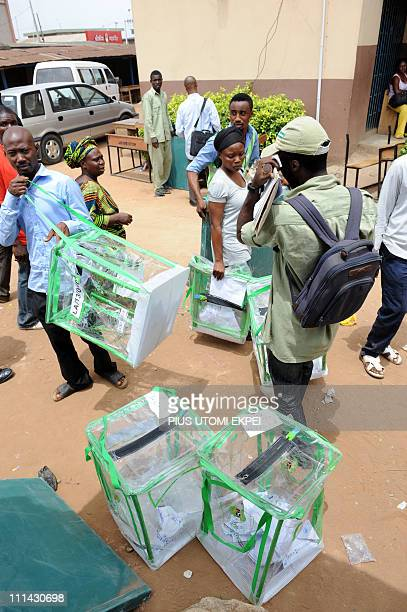 Officials of the Nigerian Independent National Electoral Commission carry filled up ballot boxes at a voting centre in the Ketu district of Lagos on...
