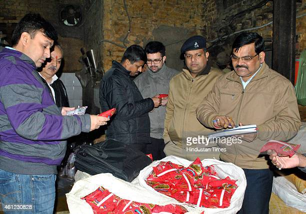 Officials of Uttar Pradesh Food and Drug department checking the stock inside a godown during a raid on January 9 2015 in Ghaziabad India Officials...
