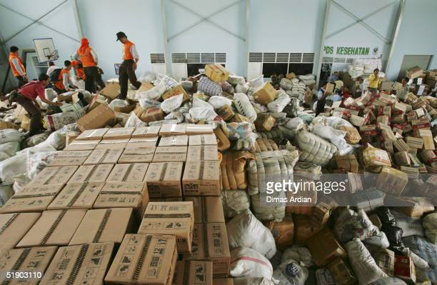 Officials pile logistical and medical supplies for earthquake and tsunami victims in the Indonesian province of Aceh as it arrives at the Polonia...