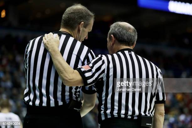 Officials Randy Heimerman and Ed Corbett meet in the second half of the game between the Vermont Catamounts and Purdue Boilermakers during the first...