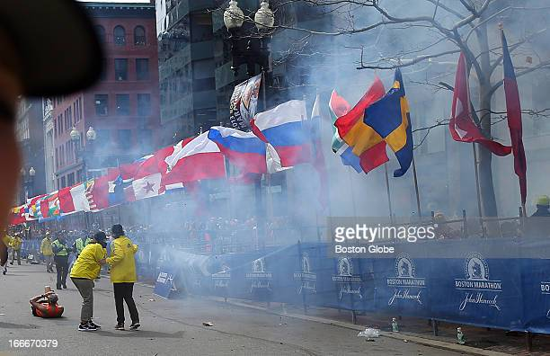 Officials react as the first explosion goes off on Boylston Street near the finish line of the 117th Boston Marathon on April 15 2013
