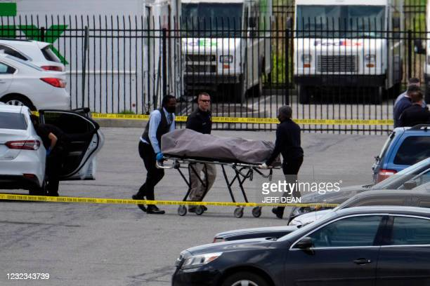 Officials recover a body at the site of a mass shooting at a FedEx facility in Indianapolis, Indiana, on April 16, 2021. - A gunman has killed at...