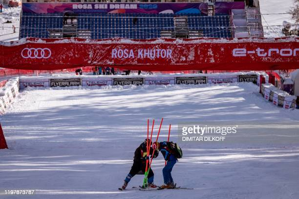 Officials remove a gate after the downhill events of the Women's Alpine Skiing World Cup were cancelled due to the course condition at the Rosa...