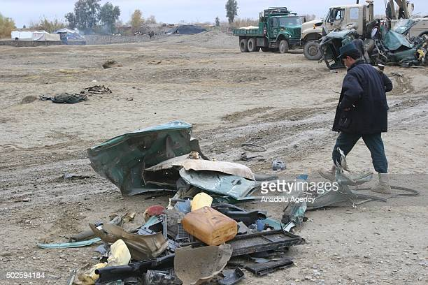 Officials remove the wreckage of police wehicle from the scene after a bomb attack killing three people including two policemen in Kolpak region in...