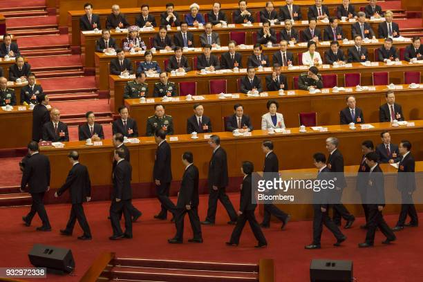 Officials return to their seats following an oathtaking ceremony at a session during the first session of the 13th National People's Congress at the...