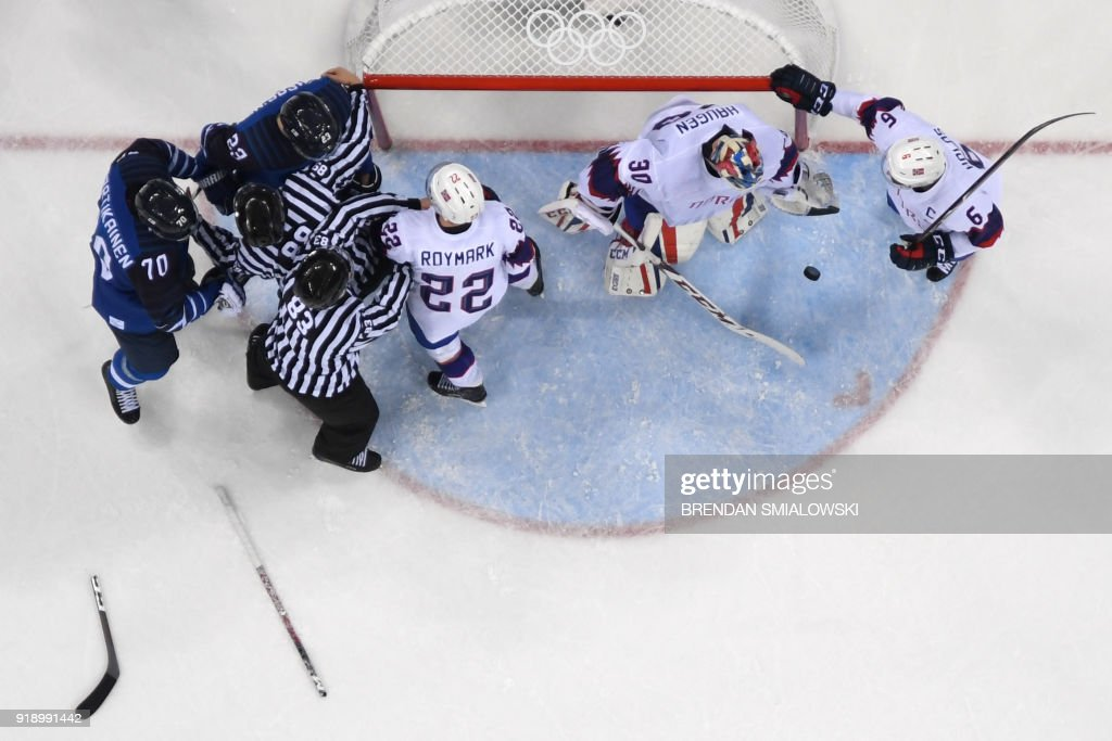 Officials separate Finland's Joonas Kemppainen (top) and Norway's Martin Roymark (3rd R) as a broken stick is seen on the ice in the men's preliminary round ice hockey match between Finland and Norway during the Pyeongchang 2018 Winter Olympic Games at the Gangneung Hockey Centre in Gangneung on February 16, 2018. / AFP PHOTO / Brendan SMIALOWSKI