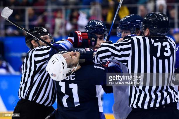 Officials separate USA's Garrett Roe and Slovakia's Michal Cajkovsky in the men's preliminary round ice hockey match between the US and Slovakia...