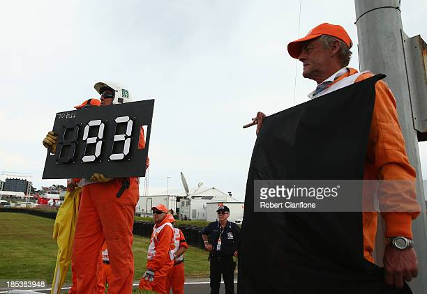 Officials show the black flag to Marc Marquez of Spain as he was disqualified for pitting one lap too late during the Australian MotoGP race at...