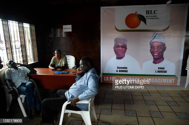 Officials sit beside a campaign poster with photographs of the opposition Dynamics Restoring Confidence party candidate, Corentin Kohoue and running...