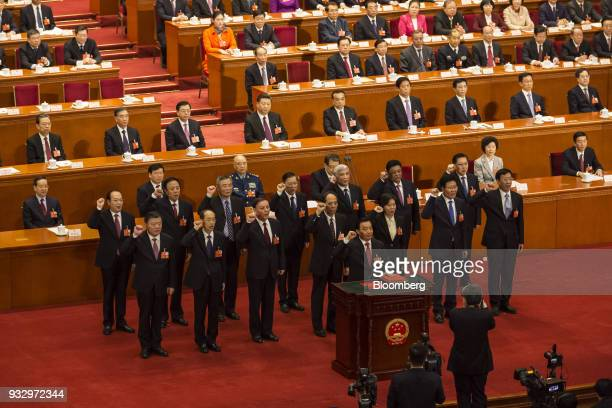 Officials speak during an oathtaking ceremony at a session during the first session of the 13th National People's Congress at the Great Hall of the...