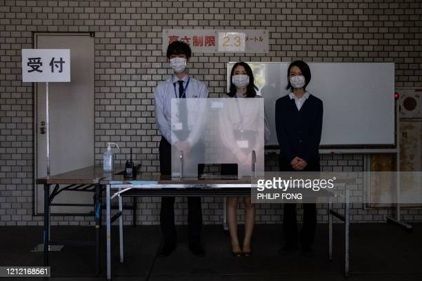 TOPSHOT Officials stand at the reception with a plastic plate during a demonstration of the polymerase chain reaction swab test for the COVID19...