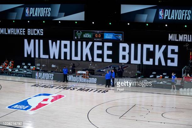 Officials stand beside an empty court after the scheduled start of game five between the Milwaukee Bucks and the Orlando Magic in the first round of...