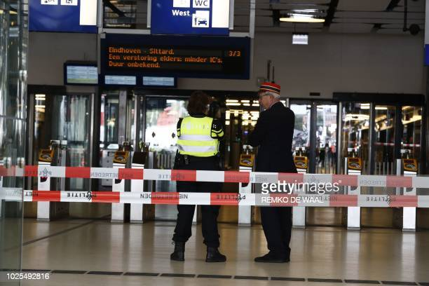 Officials stand inside a cordonnedoff area at The Central Railway Station in Amsterdam on August 31 after two people were injured in a stabbing...