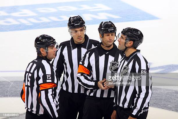 Officials Stephane Auger Bryan Pancich Chris Lee and Steve Miller meet at center ice before puck drop to start the second period between the Winnipeg...