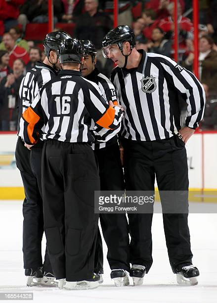 Officials Steve Barton Brian Pochmara Justin St Pierre and Brian Mach discuss a Carolina Hurricanes goal that was overturned on further review during...
